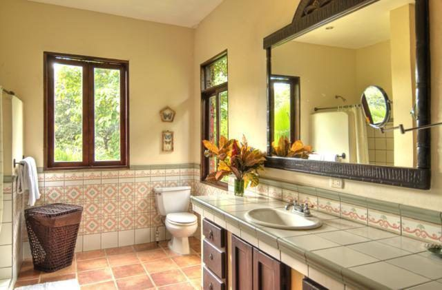 This is a simple and homey bathroom with beige walls to complement the dark wooden elements of the vanity, mirror, doors and windows. Images courtesy of Toptenrealestatedeals.com.