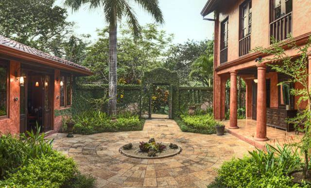 This view of the front courtyard shows the gorgeous arched main gate adorned with shrubs and tall trees. Images courtesy of Toptenrealestatedeals.com.