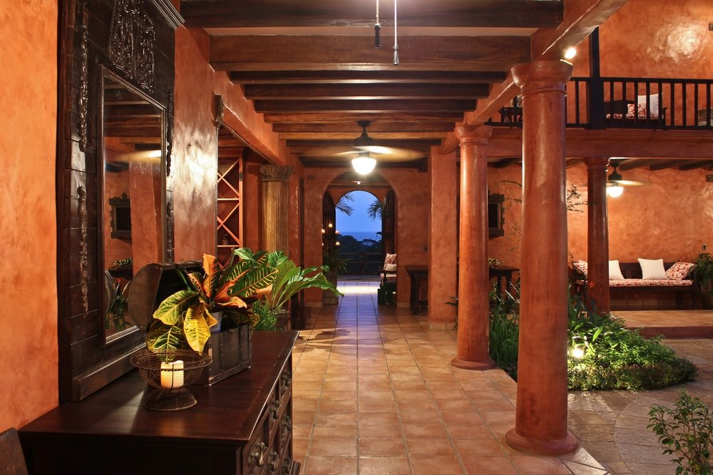 This is a nighttime look at the hallway just beside the front courtyard. The warm lighting of the beamed ceiling gives character to the earthy pillars. Images courtesy of Toptenrealestatedeals.com.