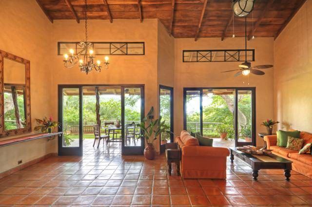 This is the spacious living room that has a tall wooden ceiling, tall beige walls and terracotta flooring tiles bathed in natural light from the glass doors. Images courtesy of Toptenrealestatedeals.com.