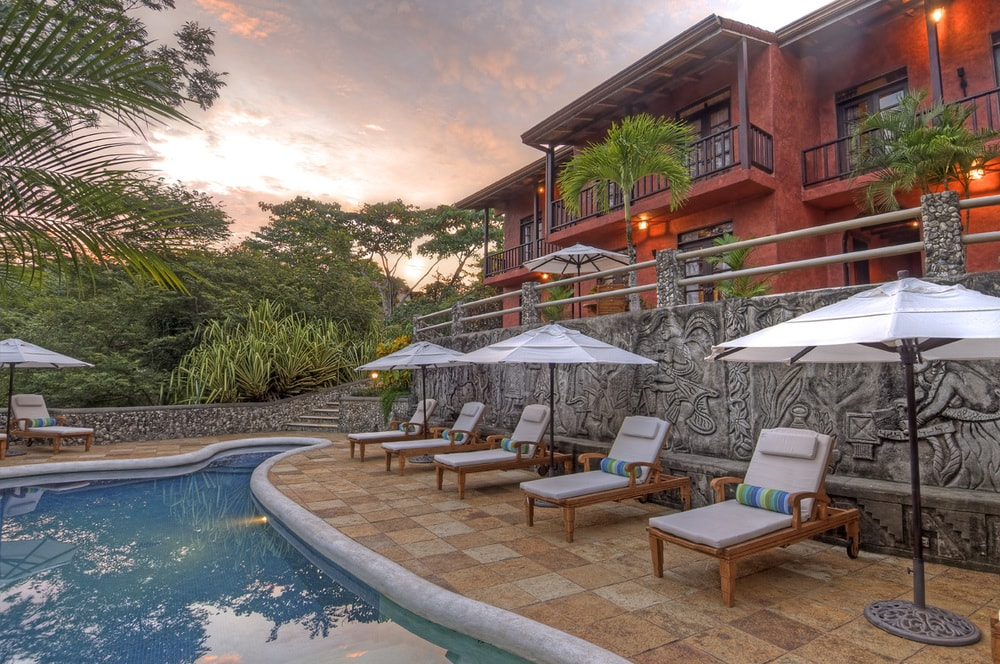 This is the beautiful poolside of the main house with a vibrant reddish tone to its exterior walls that contrast the surrounding lush landscape of tropical trees. Images courtesy of Toptenrealestatedeals.com.