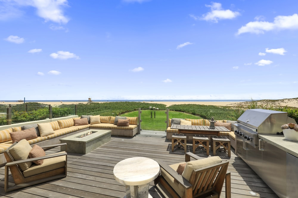 This is the backyard patio with a wooden deck floor. It has an L-shaped built-in cushioned bench beside the modern firepit. Images courtesy of Toptenrealestatedeals.com.