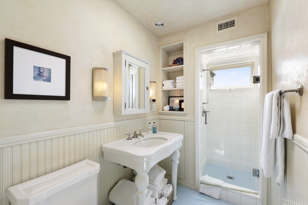 This is a simple yet charming bathroom with wainscoting to its beige walls that complement the white porcelain sink and toilet. On the far side is the glass door of the walk-in shower area. Images courtesy of Toptenrealestatedeals.com.