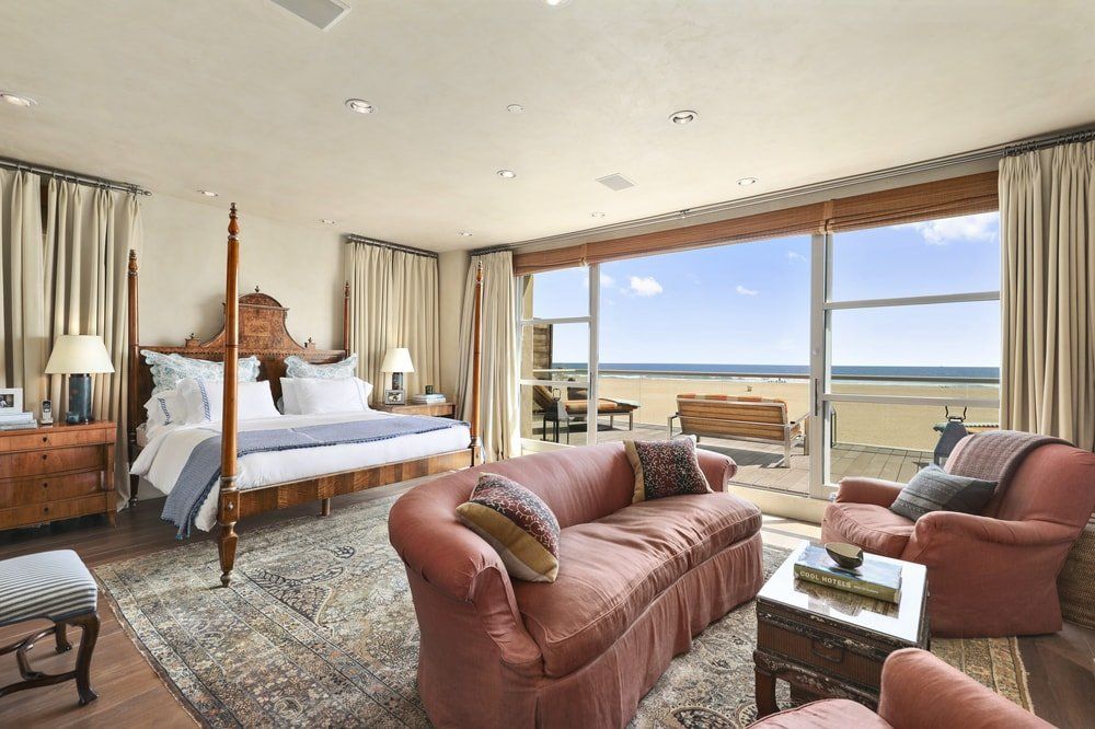 The primary bedroom has a large wooden four-poster bed with a sitting area across from it. On the side is a wide open wall that leads to the balcony. Images courtesy of Toptenrealestatedeals.com.