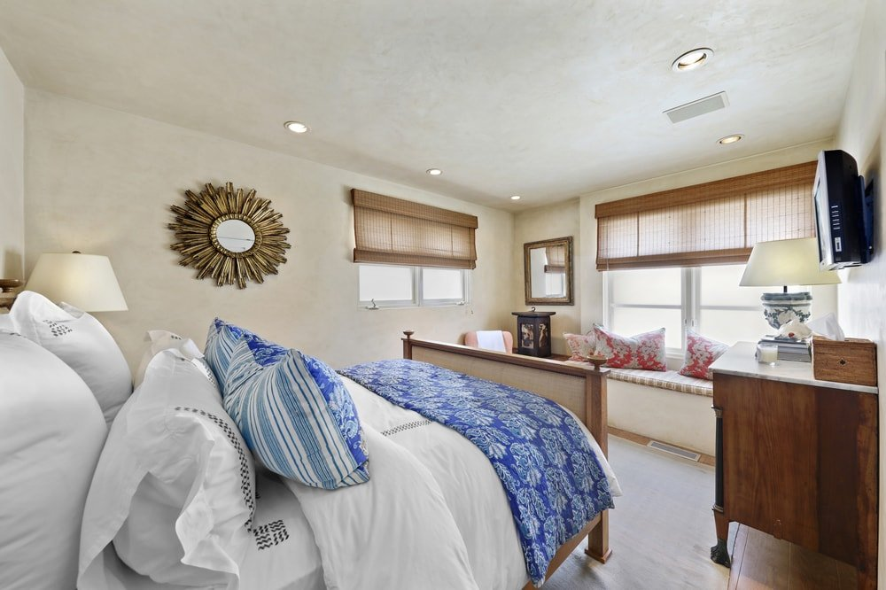 This bedroom has a wooden sleigh bed complemented by the charming reading nook across from it under the window with a built-in cushioned seat. Images courtesy of Toptenrealestatedeals.com.