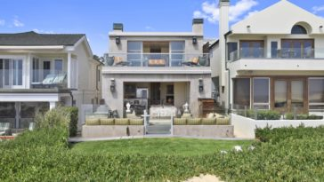 This is the front view of the charming beach house with a warm gray exterior complemented by the glass balcony railing and the concrete planters at the front porch. Images courtesy of Toptenrealestatedeals.com.