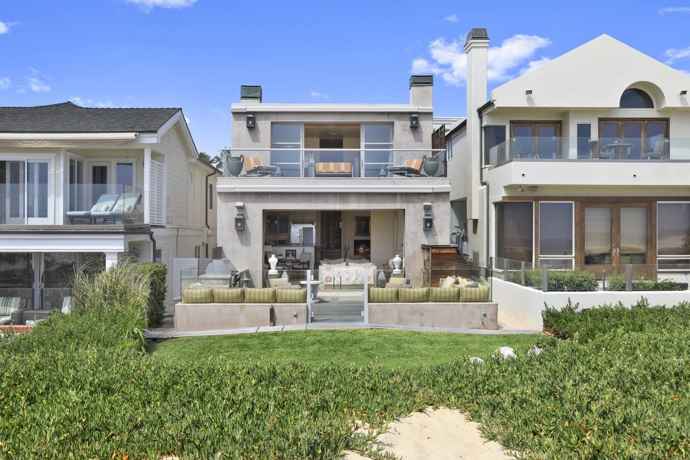 This is the back view of the charming beach house with a warm gray exterior complemented by the glass balcony railing and the glass walls of the back patio. Images courtesy of Toptenrealestatedeals.com.