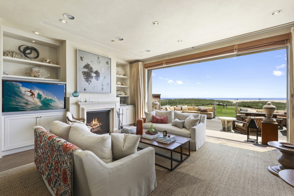 This living room has a couple of beige cushioned sofas and a coffee table across from the beige fireplace topped with a beautiful painting and flanked with built-in cabinetry. Images courtesy of Toptenrealestatedeals.com.