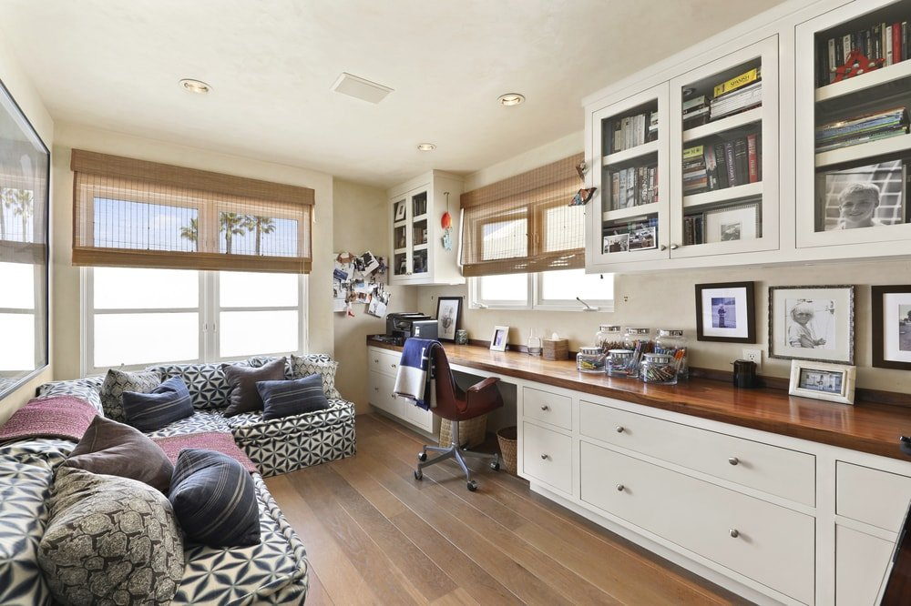 This is the homey and charming home office with a built-in wooden beige structure with cabinets,drawers and a desk made of wood to match the hardwood flooring adorned with an L-shaped sofa on the other side of the room. Images courtesy of Toptenrealestatedeals.com.