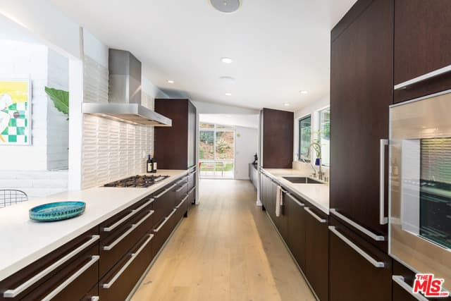 The dark brown tone of the modern cabinetry stands out against the light hardwood flooring and the white shed ceiling of this long and narrow kitchen with a stainless steel vent over the cooking area.