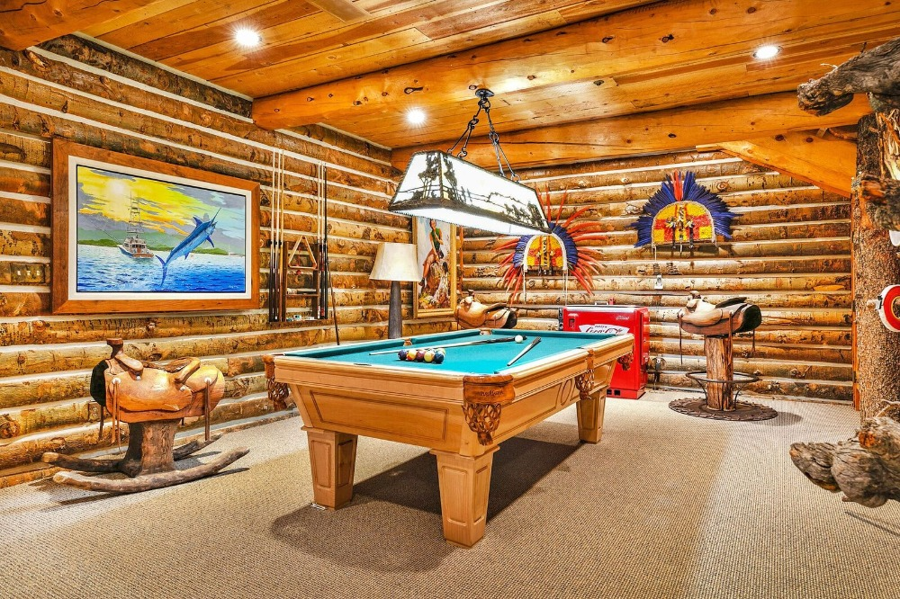 A focused look at the home's billiards table surrounded by logs walls. Images courtesy of Toptenrealestatedeals.com.