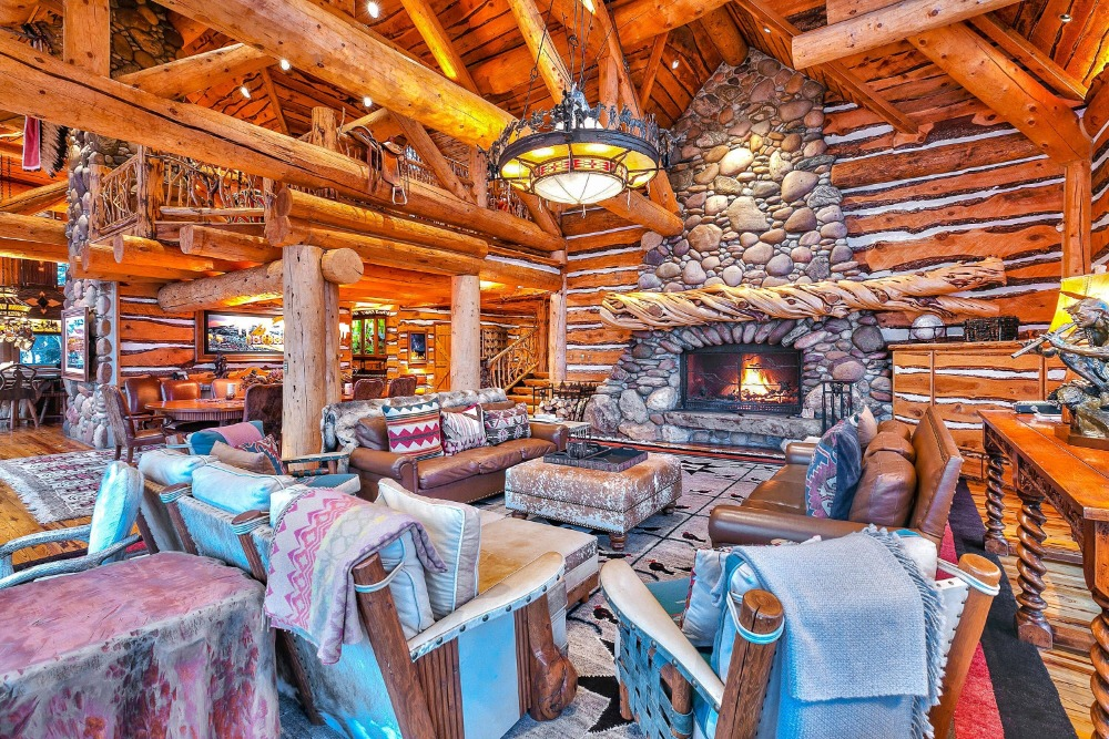 A great room featuring a large living space with a cozy seats and a fireplace, along with a round dining table set. Images courtesy of Toptenrealestatedeals.com.