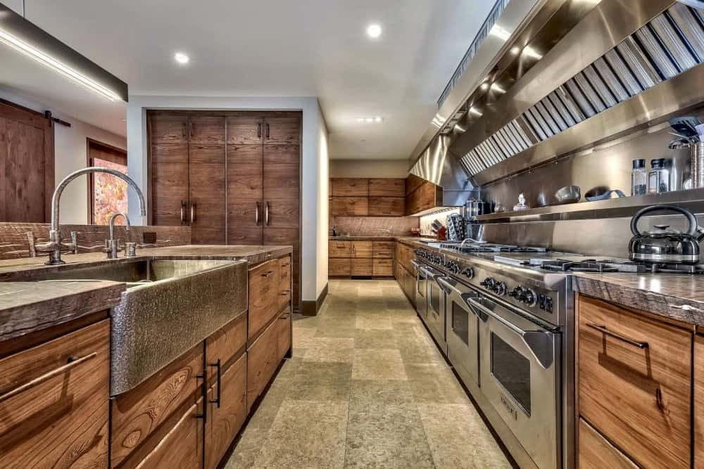 This gorgeous long and narrow kitchen has dark brown cabinetry complemented by the modern stainless steel appliances topped with a bright white ceiling with recessed lights.