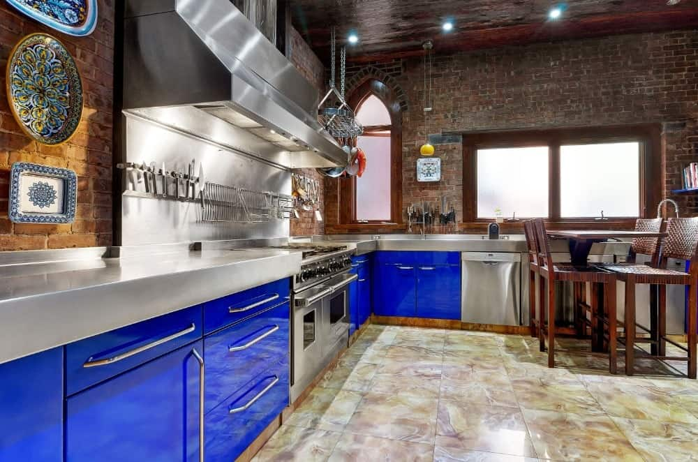 This is a gorgeous Industrial-style kitchen with exposed brick walls to complement the stainless steel surfaces and sleek blue cabinetry. On the far end is a built-in small table paired with matching wooden chairs that has a red tone.
