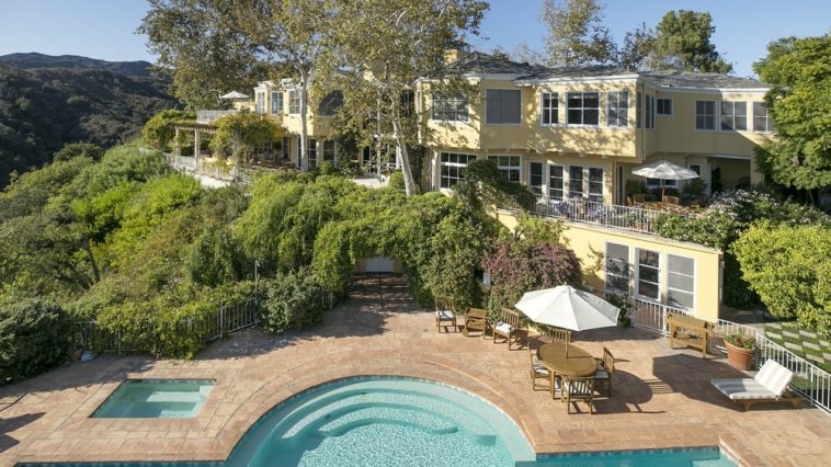 This aerial view of the back of the house features the beautiful swimming pool along with the lush green landscaping that complements the beautiful beige exterior walls of the house. Images courtesy of Toptenrealestatedeals.com.