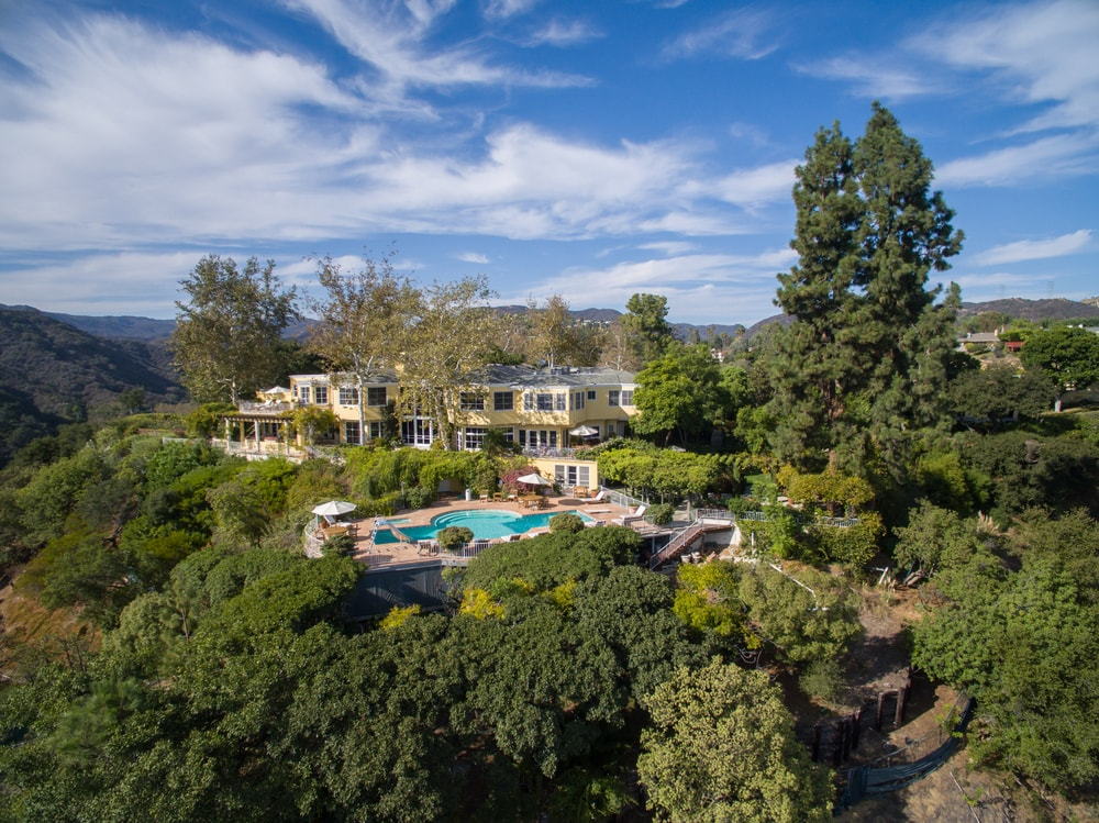 This aerial view of the estate features the level of isolation and privacy of the house afforded by the lush surrounding landscape of tall trees. Images courtesy of Toptenrealestatedeals.com.