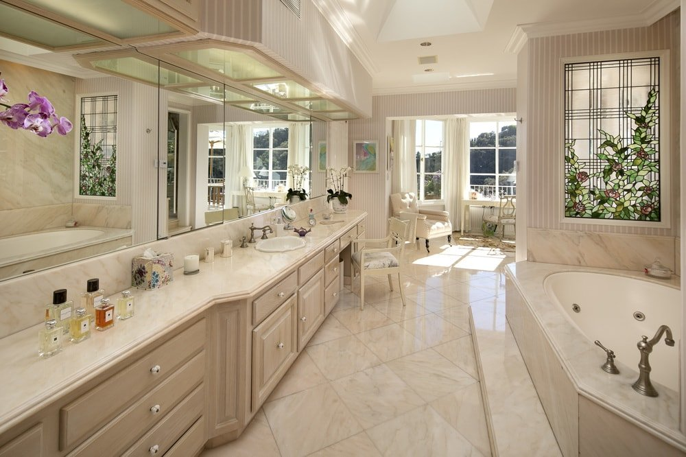 This is a grand and luxurious primary bathroom with a consistent beige marble tone to its flooring tiles, bathtub housing, walls and the large vanity. Images courtesy of Toptenrealestatedeals.com.