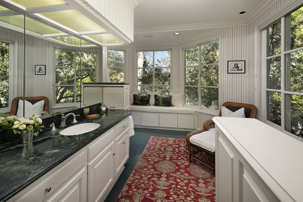 This bathroom has a dark countertop to its vanity. This matches well with the dark tone of the floor that is complemented by the patterned area rug and the woven wicker armchair on the corner. Images courtesy of Toptenrealestatedeals.com.