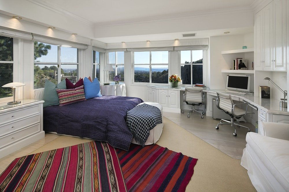 This charming and bright bedroom has a light tone to its tray ceiling, walls and hardwood flooring. These are then augmented by the bed, patterned area rugs and the built-in desks across from the bed. Images courtesy of Toptenrealestatedeals.com.