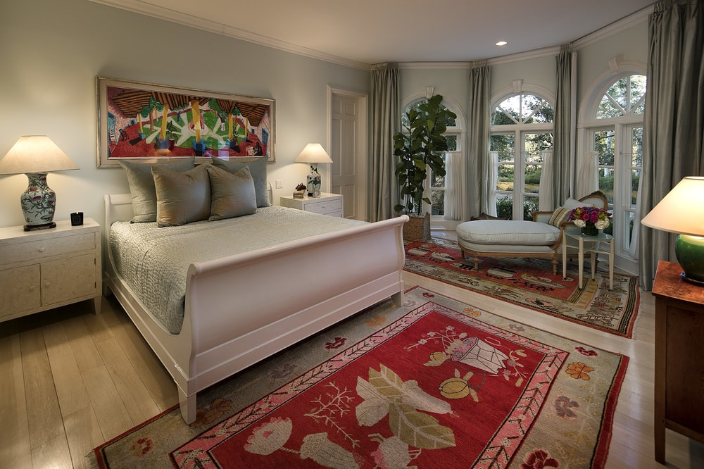 This bedroom's beige sleigh bed and matching day bed by the arched window are complemented by the colorful patterned area rug, headboard and the potted plant by the window. Images courtesy of Toptenrealestatedeals.com.