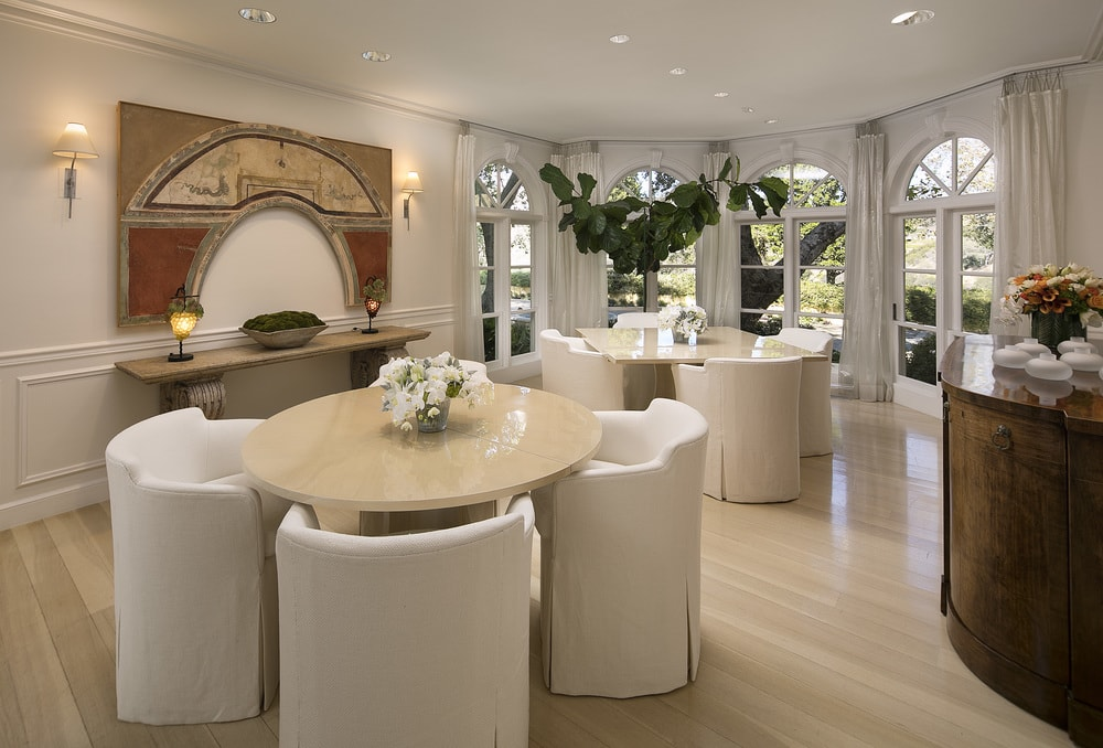 This dining room has a couple of round wooden dining table with their own matching cushioned chairs with beige slipcovers to go well with the light hardwood flooring. Images courtesy of Toptenrealestatedeals.com.