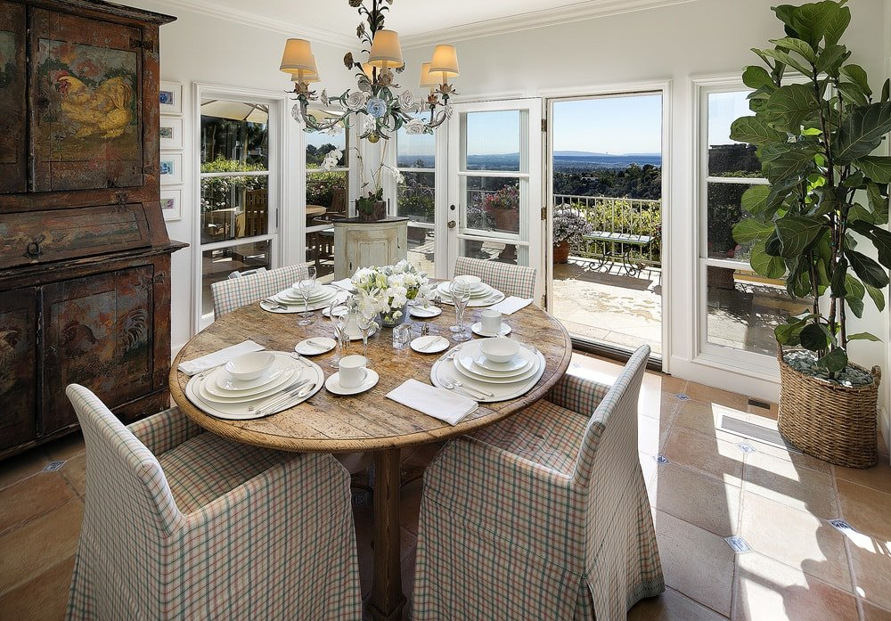 This dining area has a charming round wooden dining table surrounded by cushioned chairs that has patterned slipcovers. These are then complemented by the chandelier and the surrounding glass windows. Images courtesy of Toptenrealestatedeals.com.