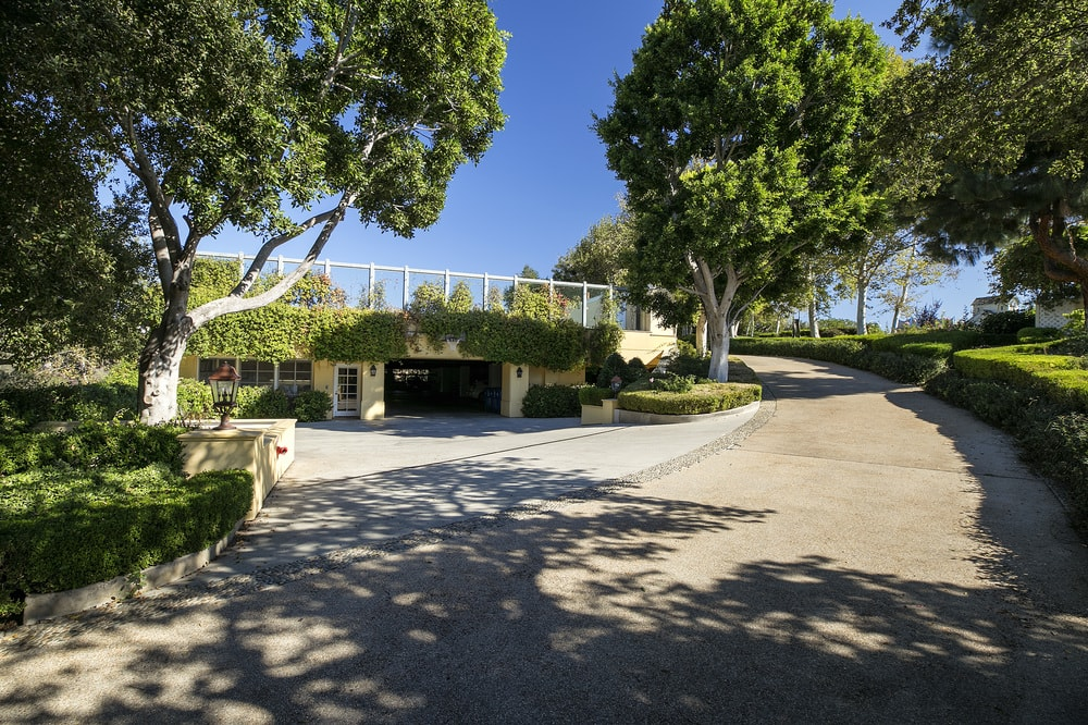 This is the view of the entrance to the car garage from the vantage of the driveway. You can see here that the entrance is festooned with creeping plants and tall trees giving it a welcoming and relaxing vibe. Images courtesy of Toptenrealestatedeals.com.