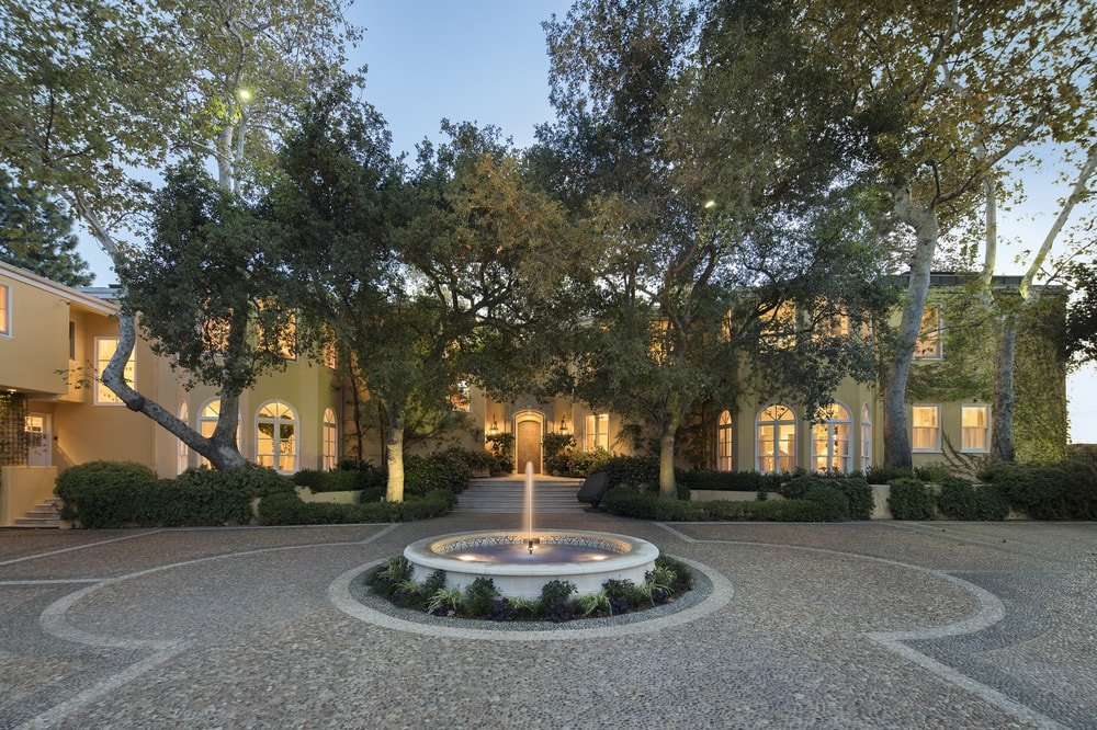 This is the front view of the house showcasing the lovely round fountain in the middle of the large concrete courtyard and driveway surrounded by tall trees. Images courtesy of Toptenrealestatedeals.com.