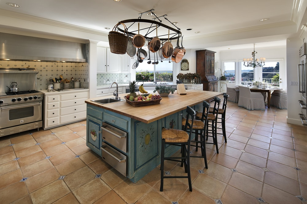 This charming kitchen has a gray kitchen island and breakfast bar in the middle of the terracotta tiles of the floor. This is complemented by the wooden butcher block countertop and hanging pot rack. Images courtesy of Toptenrealestatedeals.com.