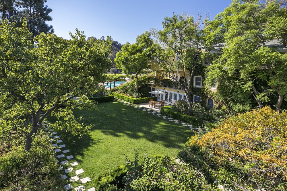 This is the lovely lawn of grass by the house with chessboard walkway and surrounding tall trees that give it a lush and relaxing vibe. Images courtesy of Toptenrealestatedeals.com.
