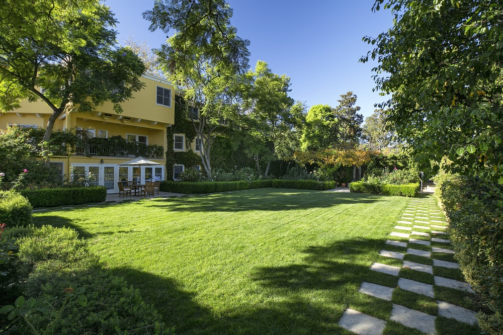 This is a close look at the lawn of grass just outside the house bordered with concrete chessboard walkways along with tall trees. Images courtesy of Toptenrealestatedeals.com.
