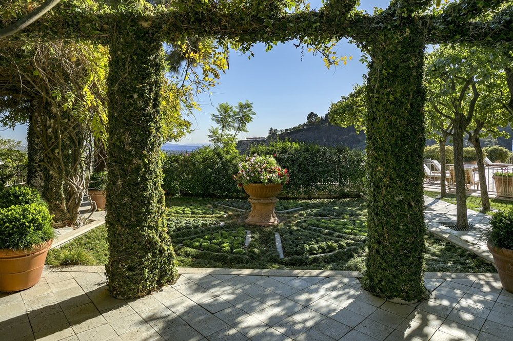 This is a close look at the elegant landscaping that has a set of trellises covered with creeping plants to match the lovely garden with a potted plant in the middle. Images courtesy of Toptenrealestatedeals.com.
