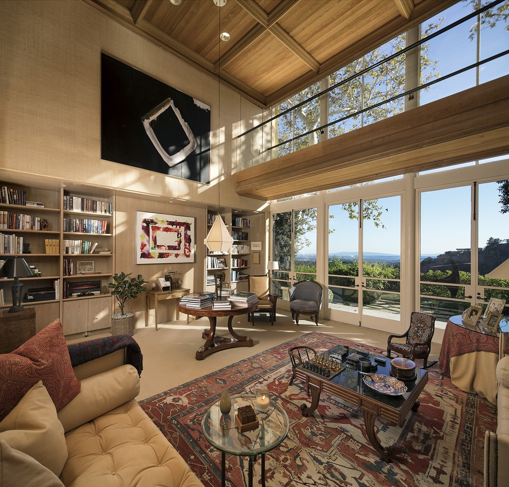 This is the spacious and airy library with a soaring high wood coffered ceiling to match the built-in shelves topped with a large painting. Images courtesy of Toptenrealestatedeals.com.