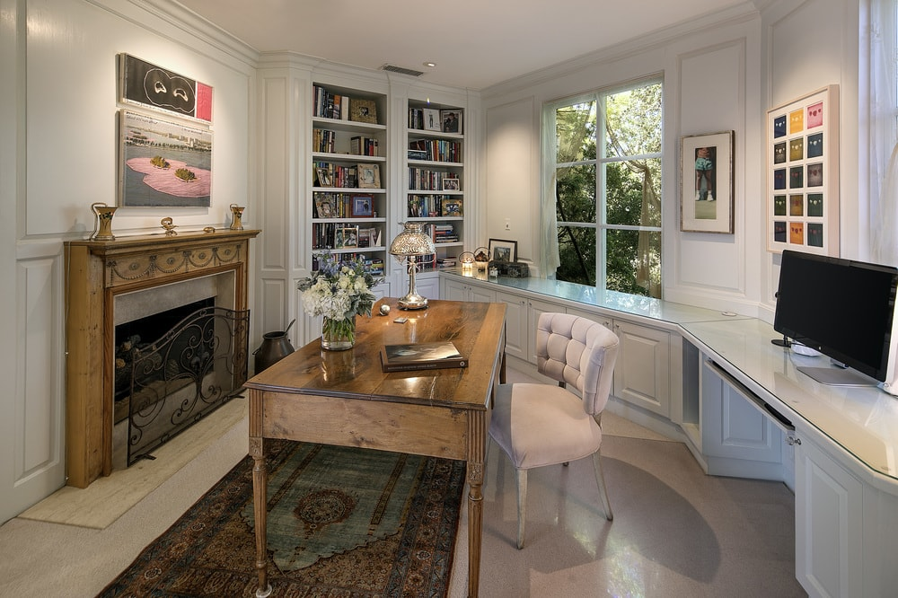 This charming and homey office has a wooden desk across from the fireplace. There is also a quiet reading nook at the corner by the window and bookshelves. Images courtesy of Toptenrealestatedeals.com.