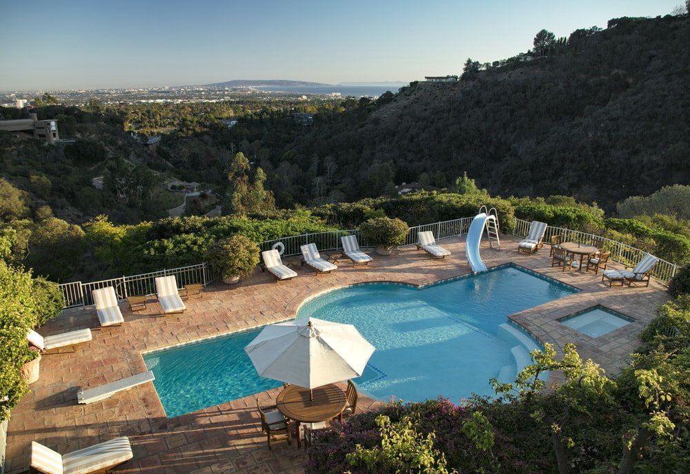 This is the view of the backyard pool from the vantage of the balcony. You can see here the lovely keyhole shape and surrounding beige walkways fitted with lawn chairs. Images courtesy of Toptenrealestatedeals.com.