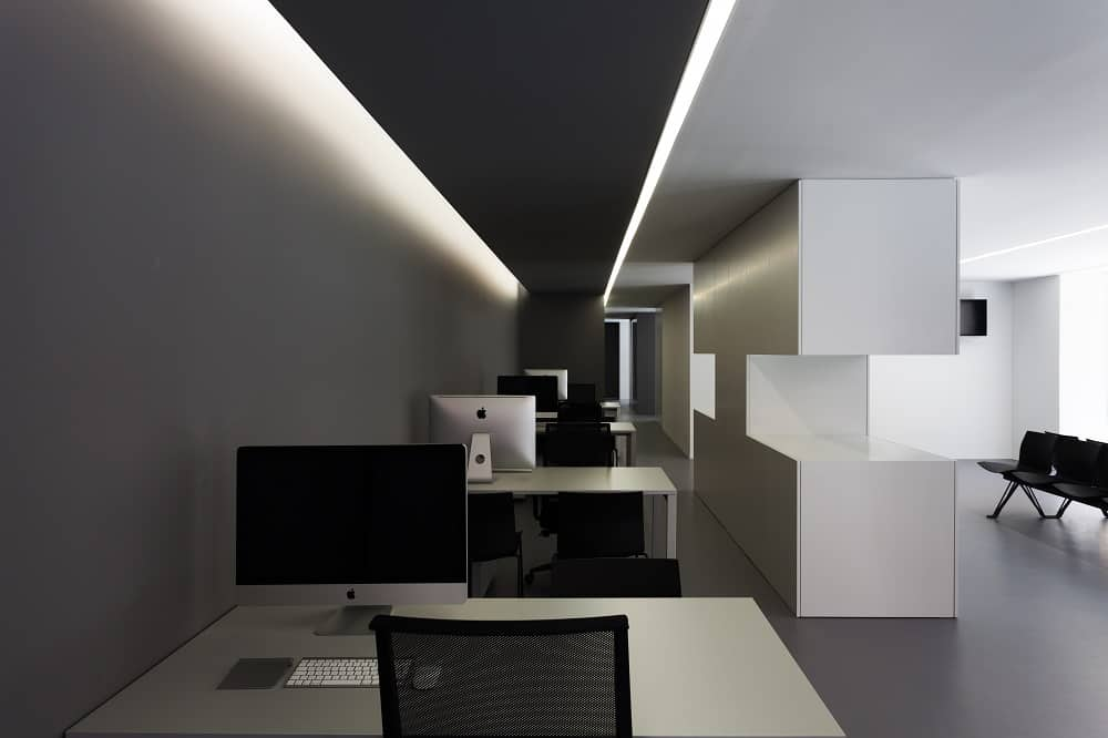 This is a view of the office with white modern built-in table to contrast the black swivel chairs and black ceiling. This is adorned with a white modern lighting on the side.