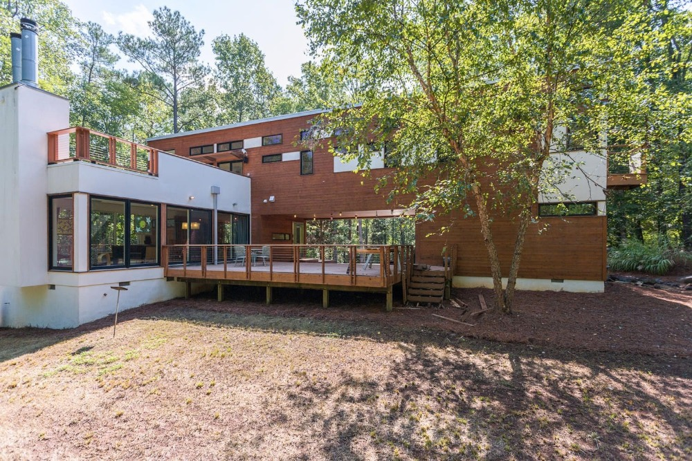 This outdoor view focuses on the home's exterior that's absolutely stunning. It has a dark brown wooden tone to its exterior walls that pair well with the surrounding landscape of tall trees. Images courtesy of Toptenrealestatedeals.com.