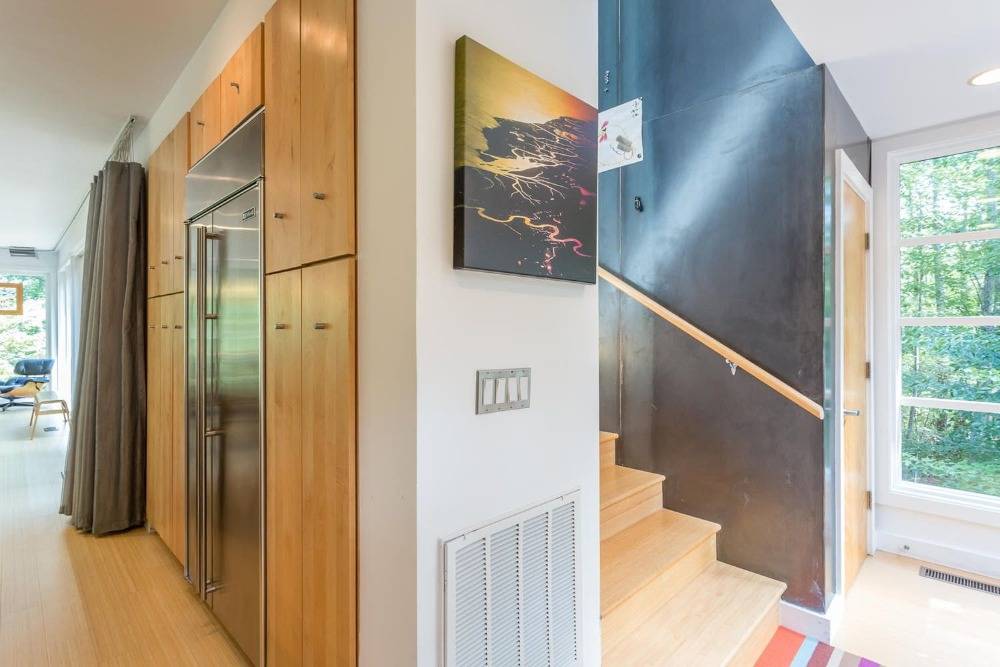 Here's a look at the staircase on the side of the kitchen. You can see here the large stainless steel fridge just around the corner from the stairs adorned with a painting. Images courtesy of Toptenrealestatedeals.com.