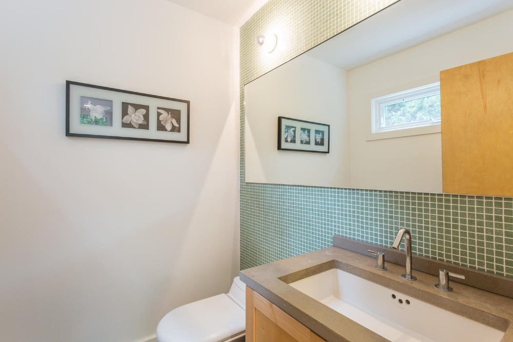 This bathroom has a sink counter and a toilet on the side, along with a mirror on the wall. Images courtesy of Toptenrealestatedeals.com.