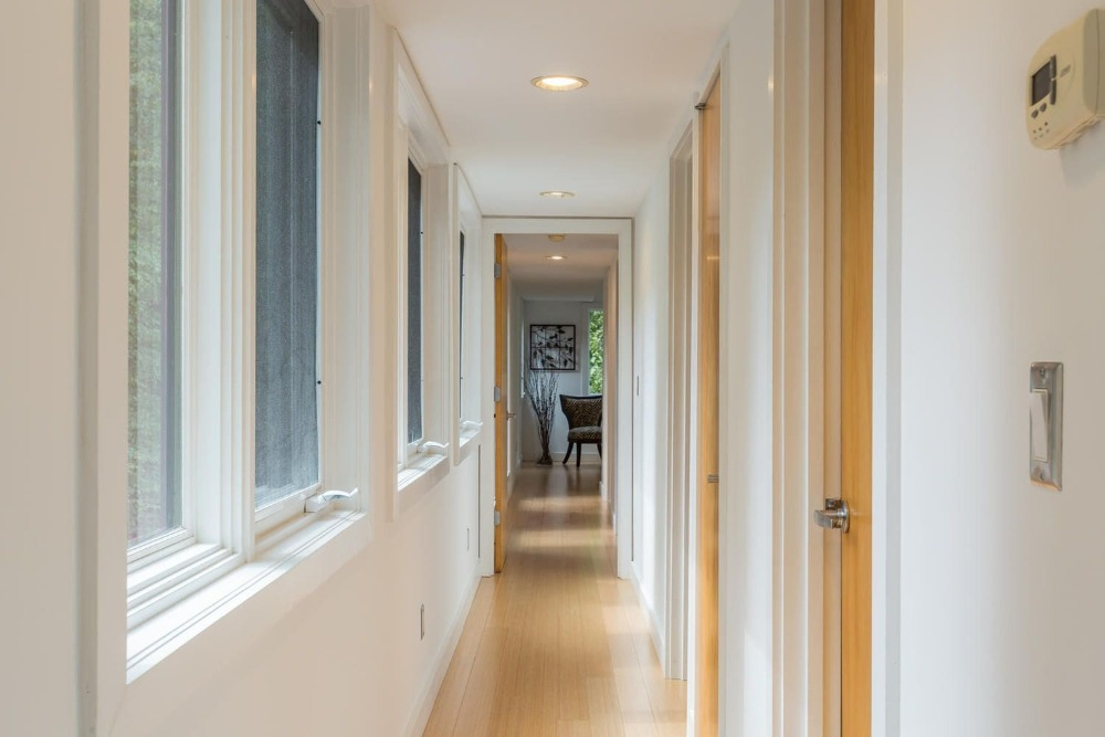 Another look at the narrow hallway facing the other direction. This shows the wooden tone of the doors that match perfectly with the light hardwood flooring augmented by recessed lights. Images courtesy of Toptenrealestatedeals.com.