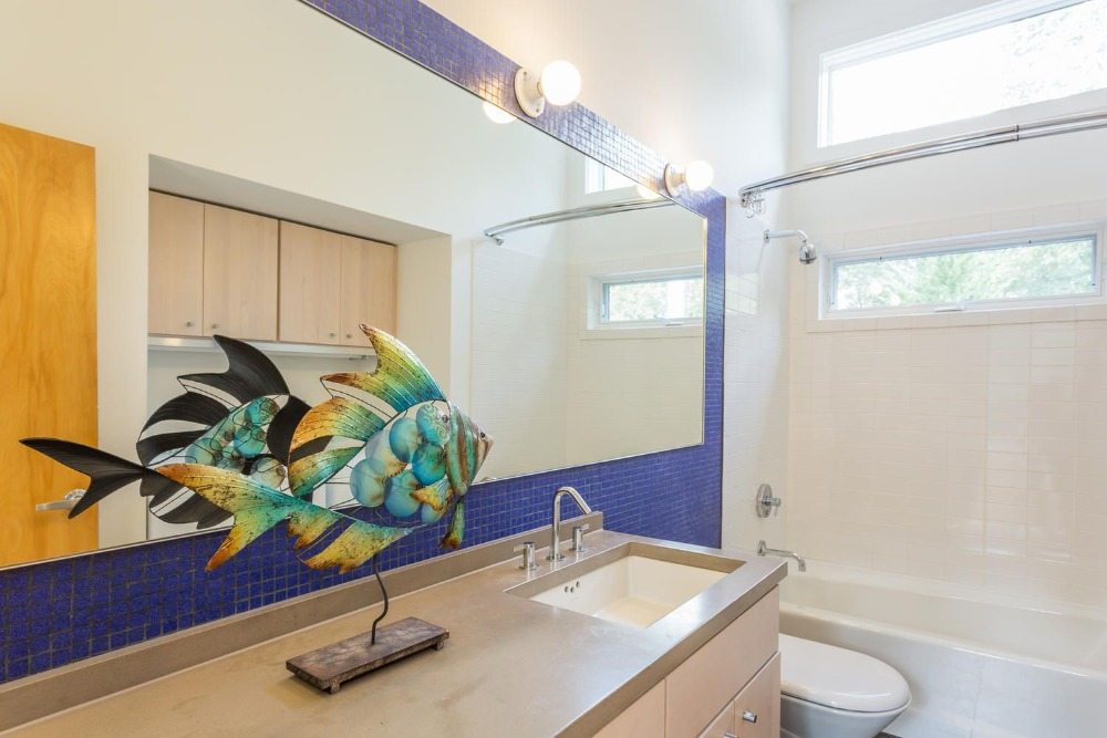 A look at this bathroom's sink counter and blue tiles wall, along with a bathtub and shower combo. Images courtesy of Toptenrealestatedeals.com.