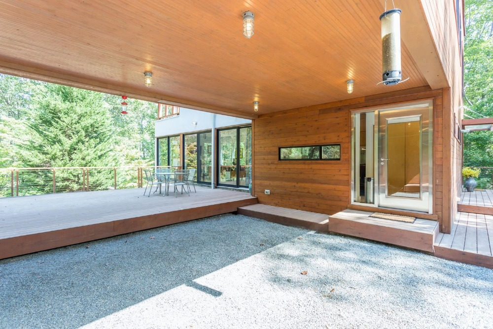 A look at the home's deck area and the entrance to the house. This area has beautiful wooden walls and a large wooden ceiling that has flush-mount lighting over the graveled walkway before transitioning to the wooden deck. Images courtesy of Toptenrealestatedeals.com.