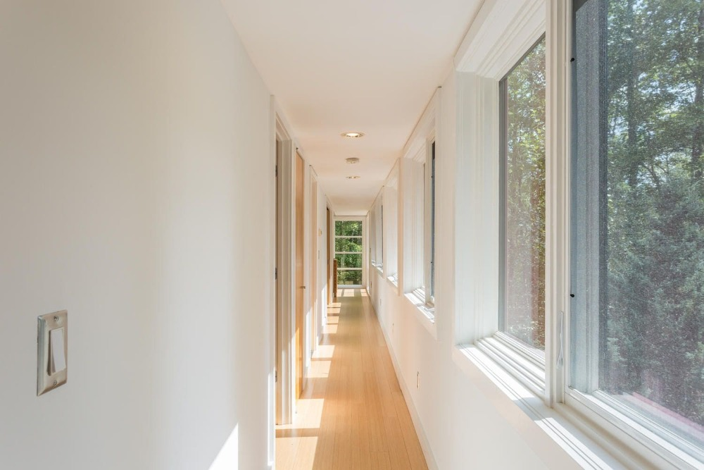 The home also has this narrow hallway with glass windows on one side to bring in natural lighting for the white walls and white ceiling. These are then complemented by the light hardwood flooring. Images courtesy of Toptenrealestatedeals.com.