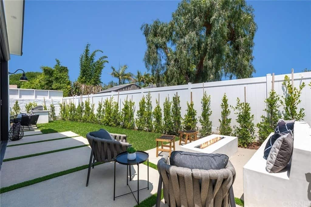 This backyard patio with an outdoor sofa and long rectangle natural-gas fuelled patio fire pit.