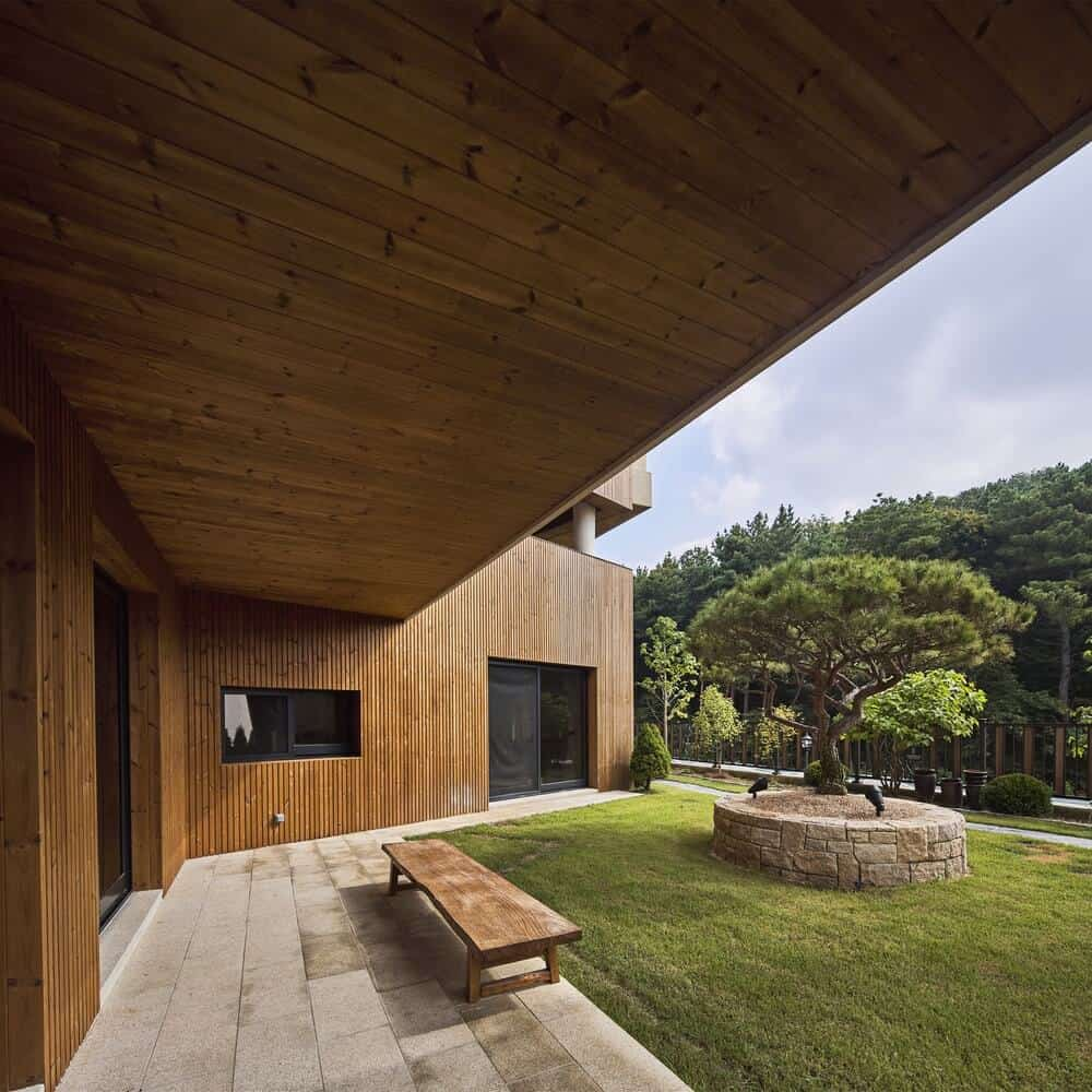 This backyard features a small wooden bench that matches the house wooden walls.