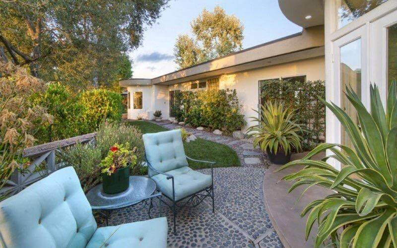 This patio with two padded comfy seats and a garden boasts many kinds of plants and mature trees.