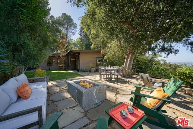 This backyard patio features a padded sofa and two green wooden chairs with a coffee table near to the built-in stone firepit.