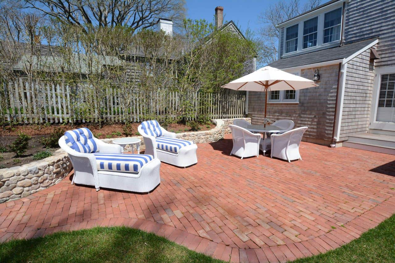 This backyard patio has a white table with a built-in umbrella paired with white chairs and red brick flooring.