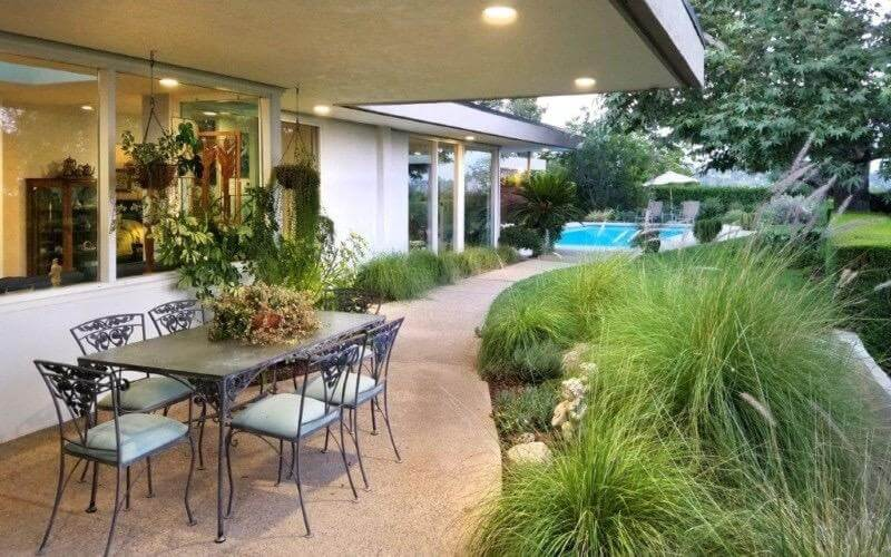 This is a flawless outside eating territory underneath a white roof with recessed lights enlightening the beige stone floors fixed with lovely arranging as an afterthought giving a pleasant foundation to the fashioned iron eating set.