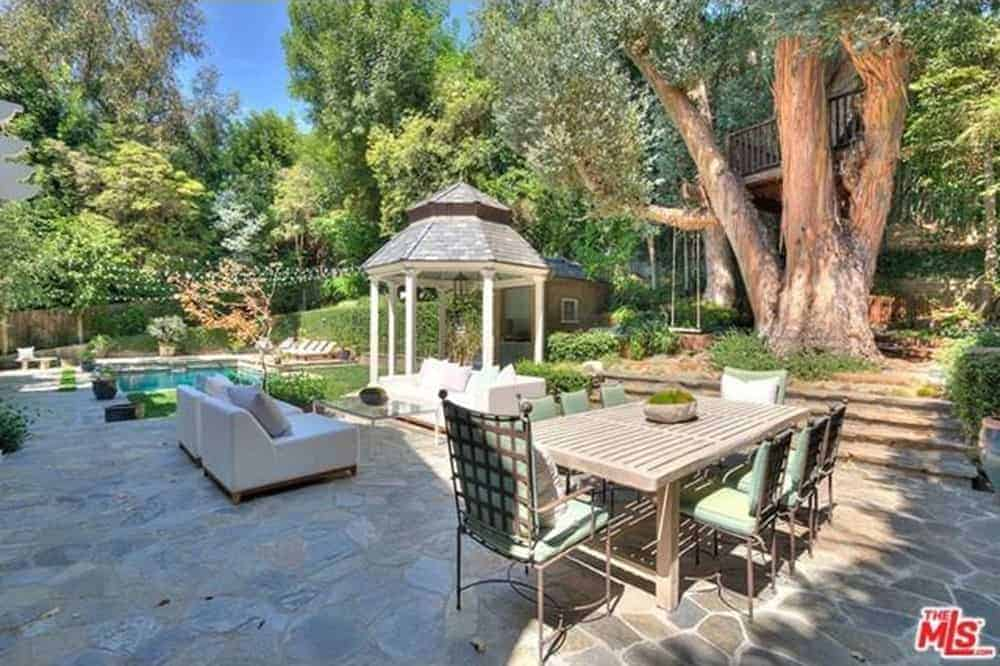 This beguiling and comfortable patio see has a feasting territory with a wooden table and fashioned iron padded seats next to a flawless sitting region